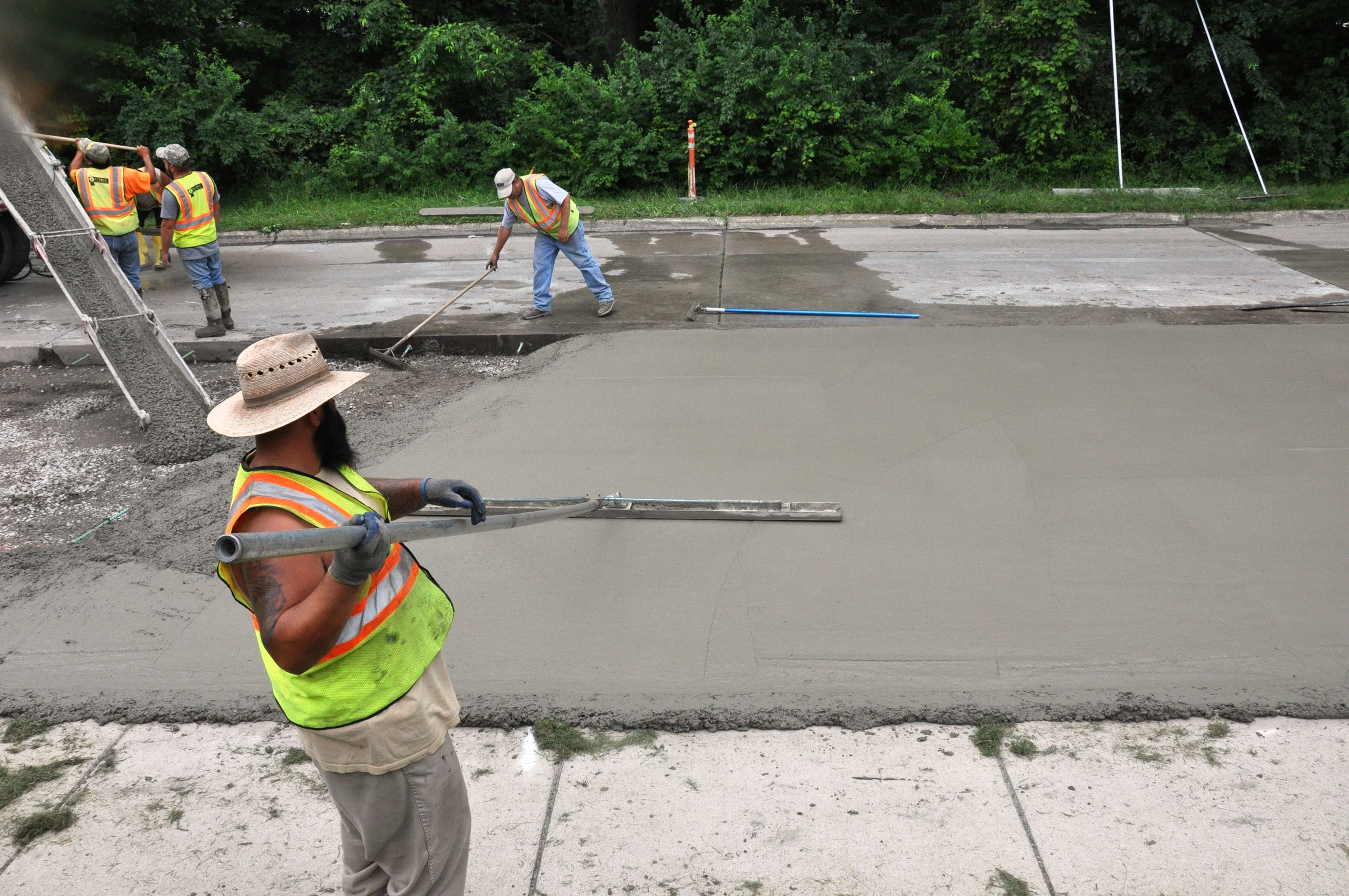 Construction workers laying concrete
